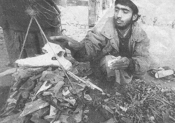 A man weighing human bones for export to Pakistan