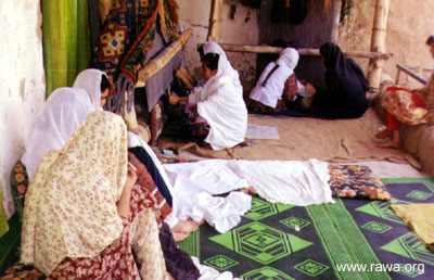 Afghan women in a RAWA carpet-weaving workplace.