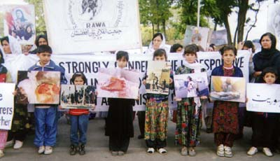 Children holding photos to describe the crimes committed by the fundamentalists in Afghanistan