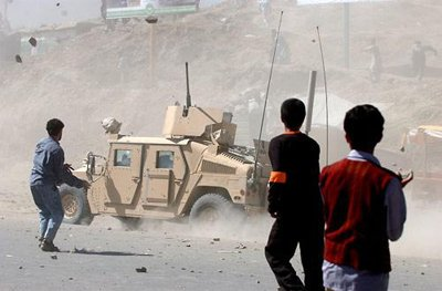 A US military Humvee speeds away under a hail of stones thrown by protestors in Kabul, Afghanistan
