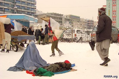 An Afghan woman with her child, begs in the bitter cold in Kabul, Afghanistan