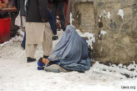 An Afghan women with her child begging in Kabul under snowfall