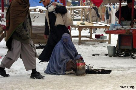 Afghan women begs in snowfall