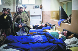 Abdul Ghafar, front, in a Mazar-e-Sharif hospital in February. Mr. Ghafar, says militiamen shot him and killed his son in order to seize his land