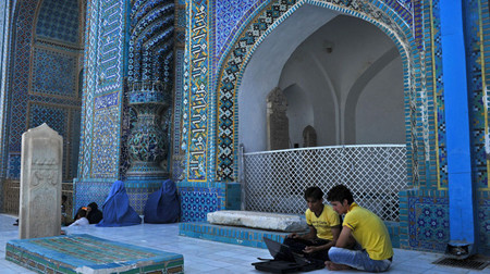 Afghan youth work on a laptop at the Rawz-e Sharif shrine in northern Mazar-e Sharif city in Balkh province