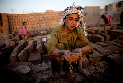 Afghan boys work at a factory making bricks used for construction in Herat, Afghanistan