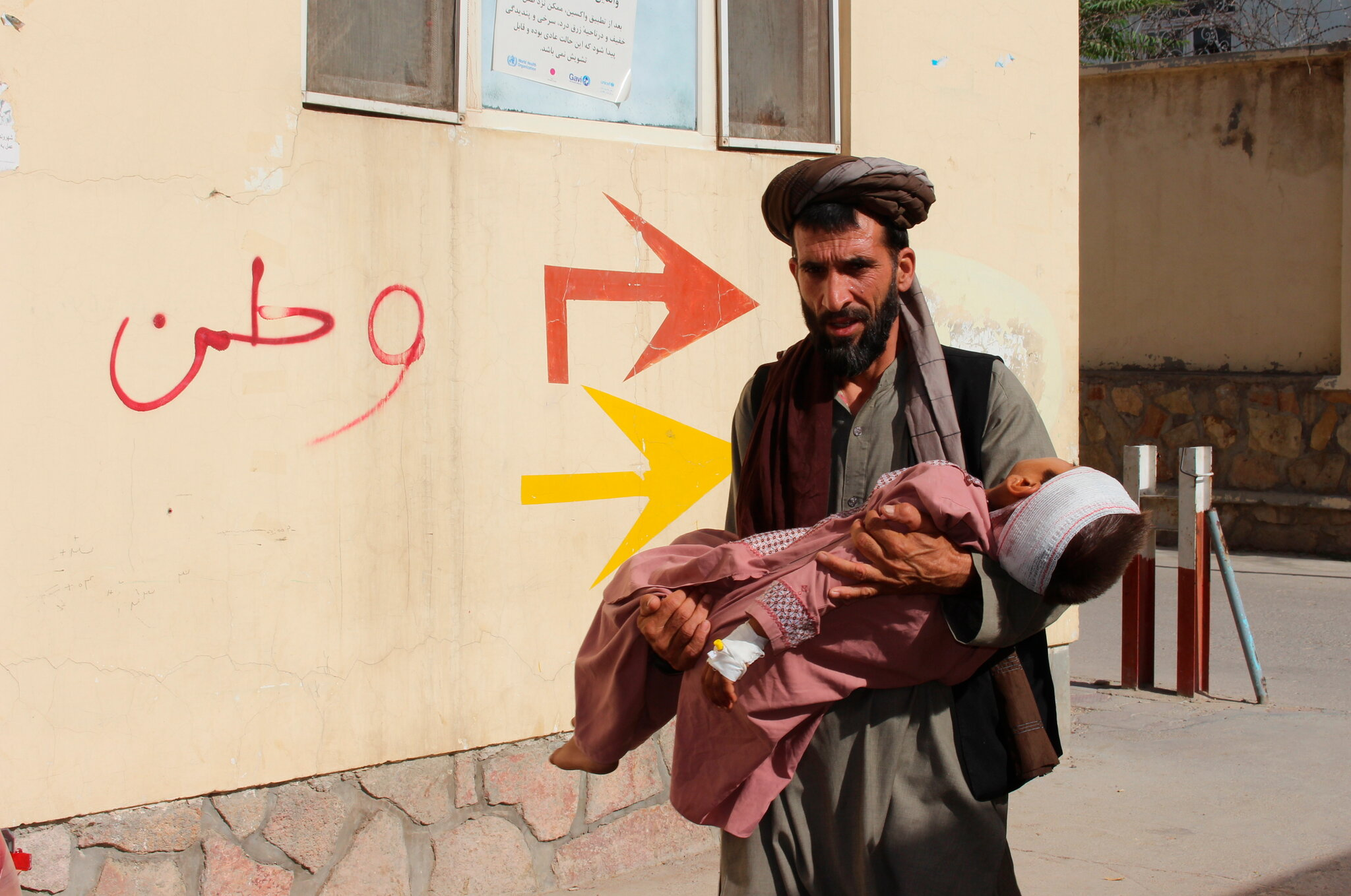 An Afghan civilian carring a wounded child to the hospital