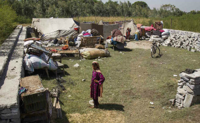 A girl stands with her family's possessions which they've brought to Afghanistan's Nangarhar province