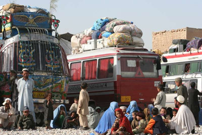 Afghan refugees wait by the buses that will take them back home