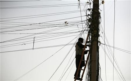 An Afghan man repairs electricity cables along the streets of Kabul November 16, 2009