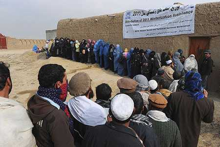 Afghans line up to receive winter supplies at a UNHCR distribution center for refugees outside Kabul