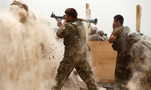 An Afghan Army soldier fires a rocket propelled grenade at suspected Taliban at combat outpost Nolen, north of Kandahar