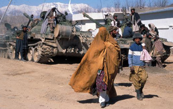 Afghan woman and boy walk by a tank in Kabul