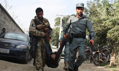Afghan security officers carried the body of a fellow officer in central Kabul, Afghanistan