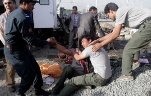 Men assisted two distraught brothers of a minibus driver killed in Kabul in a blast