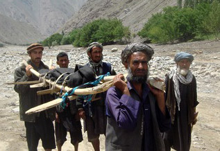 Afghan villagers transport the body of a victim after a flashflood landslide in Baghlan province