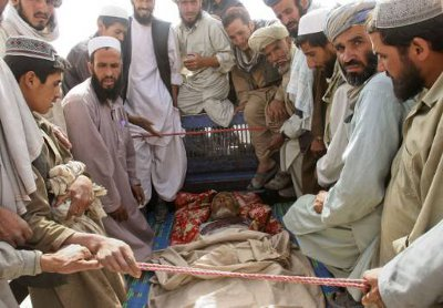 Afghans gather around the body of a man who they claim was a civilian but killed by NATO forces, during a protest in Ghazni province August 8, 2011