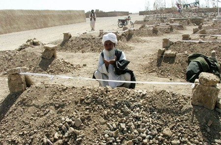 An Afghan man in Azizabad offers prayers beside graves of people killed in a US airstrike in August 2008