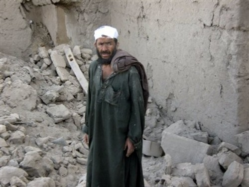A wounded Afghan villager stands amid the rubble of destroyed houses