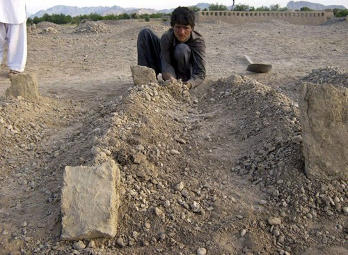 An Afghan boy places dirt over the grave of one of his family members