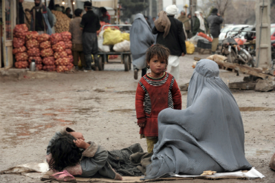 An Afghan beggar sits on the ground on a street in Herat
