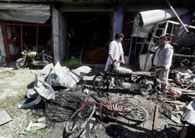 Shopkeepers survey the damage done to their businesses after a suicide attack in Kabul, Afghanistan on 24 July 2017