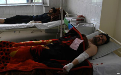 Afghan men are treated in a hospital after being injured in a car-bomb attack in Kabul on July 24, 2017