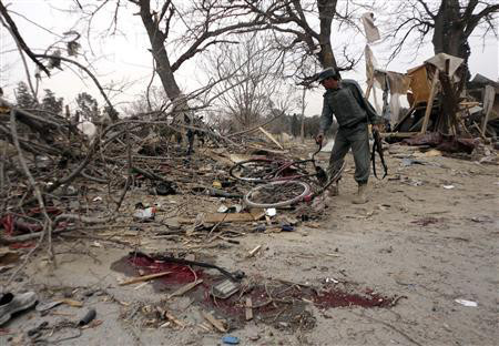 An Afghan policeman inspects the site of a suicide car bomb attack in Khost province February 18, 2011