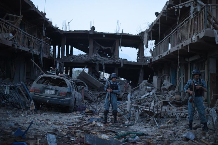 Afghan policemen stand gaurd at a market destroyed by a powerful truck bomb in Kabul