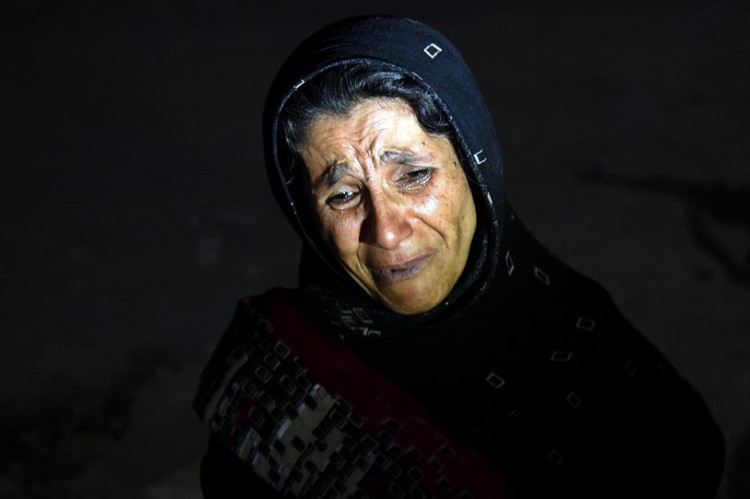 An Afghan woman cries as she looks for her son after a suicide attack