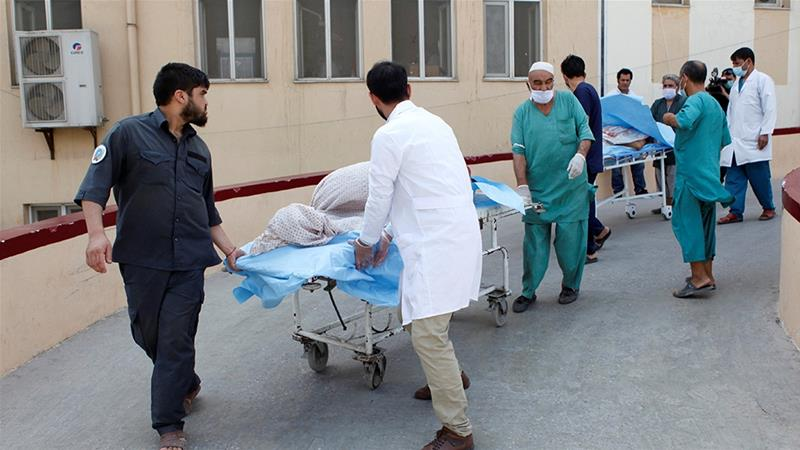 Hospital workers transfer injured people for treatment after a truck bomb blast in Balkh province on Tuesday border=