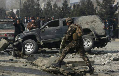 Afghan security personnel inspect the site of roadside bomb blast in Kabul, Afghanistan