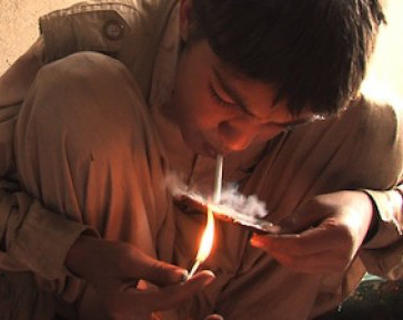 Afghan child addict taking drugs