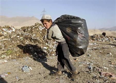 A boy carries rubbish for recycling outside Kabul December 15, 2010