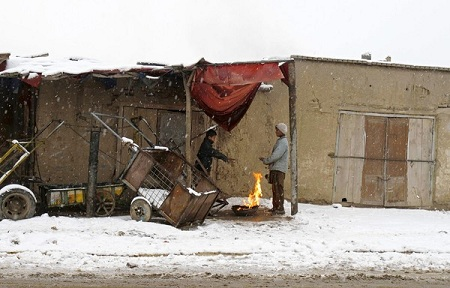 Boys warm themselves amid the morning cold on the outskirts of Kabul