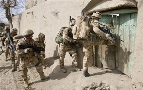 British Royal Marines of 42 Commando, break down a door during Operation Diesel