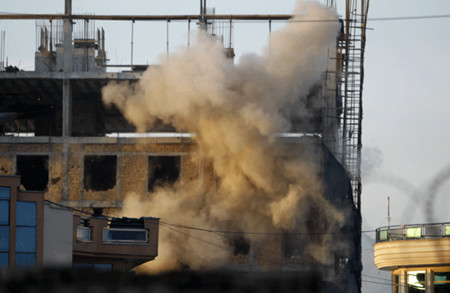 An explosion is seen at a construction site during a battle between Afghan forces and Taliban insurgents including suicide bombers in Kabul today