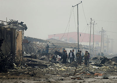 Security forces inspect the site of a car bomb attack in Kabul on Nov 29