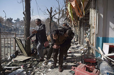 Afghan volunteers carry a body at the scene of a car bomb explosion in Kabul on Jan. 27