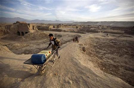 An Afghan man pushes a hand cart with water containers near a public water pump in Kabul