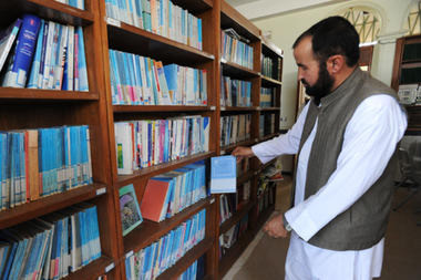 Seyed Ali Razavi, the director of a cultural center built by Iran and given to the Afghan people seven years ago, shows books of the Iranian curriculum in the library in Herat, western Afghanistan