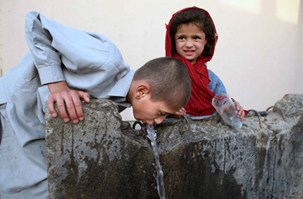 Boy drinking from common tap water in Western Kabul