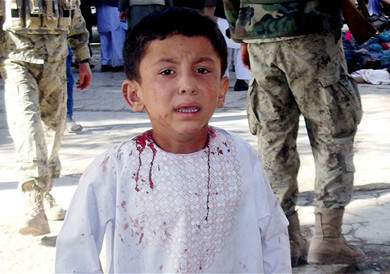 A boy, who lost his father in the suicide attack, walks around a hospital in a daze