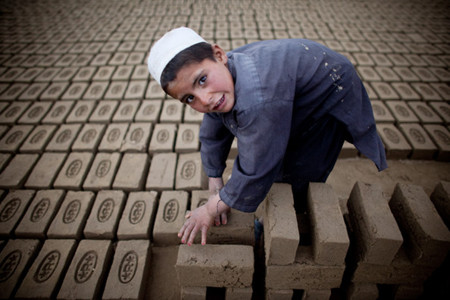 Afghan child sorts bricks at the Sadat Ltd. Brick factory, where he works from 8am to 5 pm daily in Kabul, Afghanistan