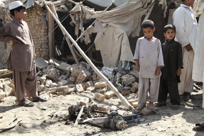 Afghan children stand near the wreckage of a vehicle after an explosion in Kandahar, south of Kabul, Afghanistan