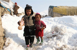 Children outside in the snow at a temporary shelter for refugees in Kabul