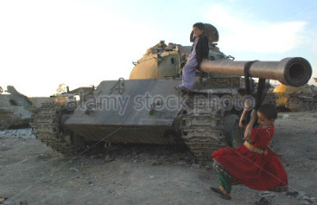 Children play on a damaged Soviet tank in Afghanistan
