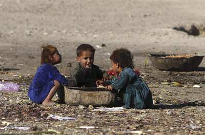 Afghan internal displaced refugee children eat food near their shelter at the outskirts of Kabul