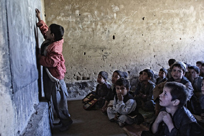 Afghan children listen to a lesson at a school near Kabul on Oct. 13, 2001