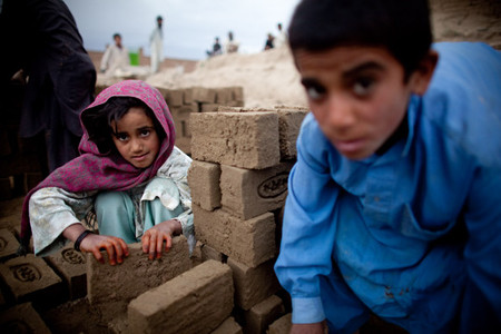 Afghan children sorts bricks at the Sadat Ltd. Brick factory, where they work from 8am to 5 pm daily, on May 14, 2010 in Kabul, Afghanistan. Child labour is common at the brick factories where the parents work as labourers, desperate to make more money enlisting their children to help doing the easy jobs.